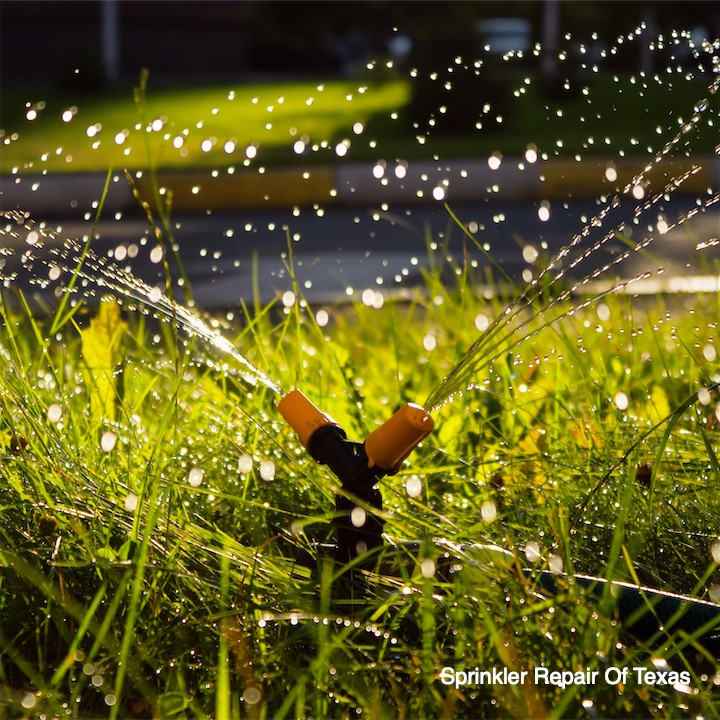 automatic-spinning-sprinkler-watering-green-grass-yard-soft-focus